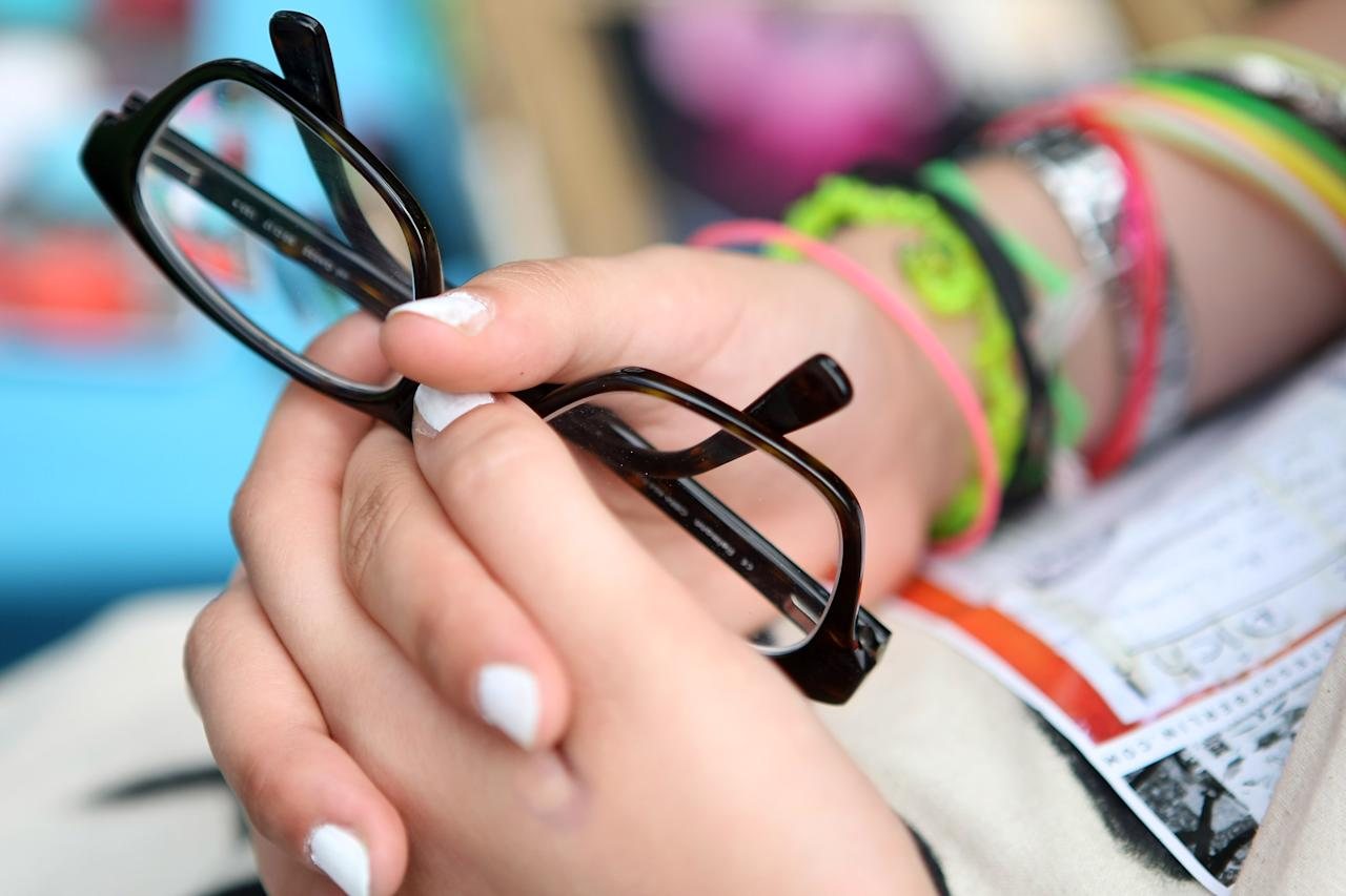 """BERLIN, GERMANY - JULY 21:  An attendee holds her pair of glasses at the second annual Hipster Olympics on July 21, 2012 in Berlin, Germany. With events such as the """"Horn-Rimmed Glasses Throw,"""" """"Skinny Jeans Tug-O-War,"""" """"Vinyl Record Spinning Contest"""" and """"Cloth Tote Sack Race,"""" the Hipster Olympics both mocks and celebrates the Hipster subculture, which some critics claim could never be accurately defined and others that it never existed in the first place. The imprecise nature of determining what makes one a member means that the symptomatic elements of adherants to the group vary in each country, but the archetype of the version in Berlin, one of the more popular locations for those following its lifestyle, along with London and Brooklyn, includes a penchant for canvas tote bags, the carbonated yerba mate drink Club Mate, analogue film cameras, an asymetrical haircut, 80s neon fashion, and, allegedly, a heavy dose of irony. To some in Berlin, members of the hipster """"movement"""" have replaced a former unwanted identity in gentrifying neighborhoods, the Yuppie, for targets of criticism, as landlords raise rents in the areas to which they relocate, particularly the up-and-coming neighborhood of Neukoelln.  (Photo by Adam Berry/Getty Images)"""