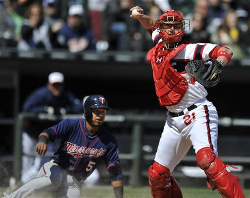 Chicago White Sox catcher Tyler Flowers, right, looks to throw to first base after forcing out Minnesota Twins' Eduardo Escobar at home plate during the seventh inning of a baseball game in Chicago, April 21, 2013. Minnesota won 5-3. (AP Photo/Paul Beaty)