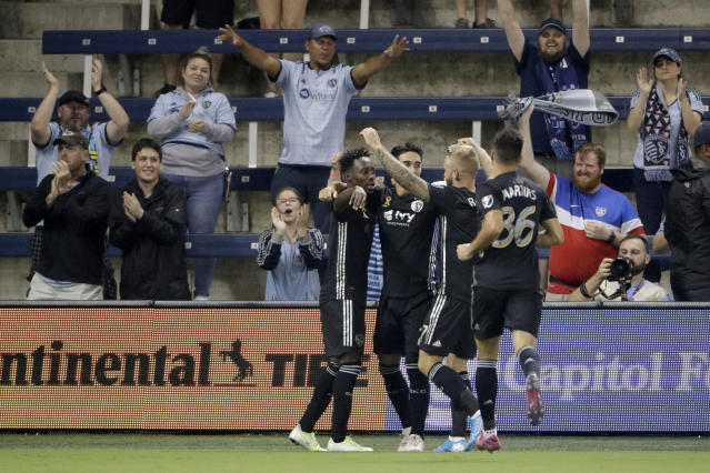 Sporting Kansas City players celebrate a goal by forward Gerso Fernandes, left, during the first half of an MLS soccer match against the Colorado Rapids on Saturday, Sept. 21, 2019, in Kansas City, Kan. (AP Photo/Charlie Riedel)