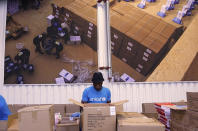 This image taken from video shows people working inside the UNICEF warehouse, the world's largest humanitarian aid warehouse, in Copenhagen, Denmark , Tuesday Oct. 13, 2020. For Burkina Faso, India, Venezuela and other countries with shaky health care delivery systems, the best chance for receiving scarce supplies of a coronavirus vaccine is through the Covax initiative, led by the World Health Organization and the Gavi vaccine alliance. UNICEF began laying the groundwork months ago in Copenhagen, at the world's largest humanitarian aid warehouse. (AP Photo)