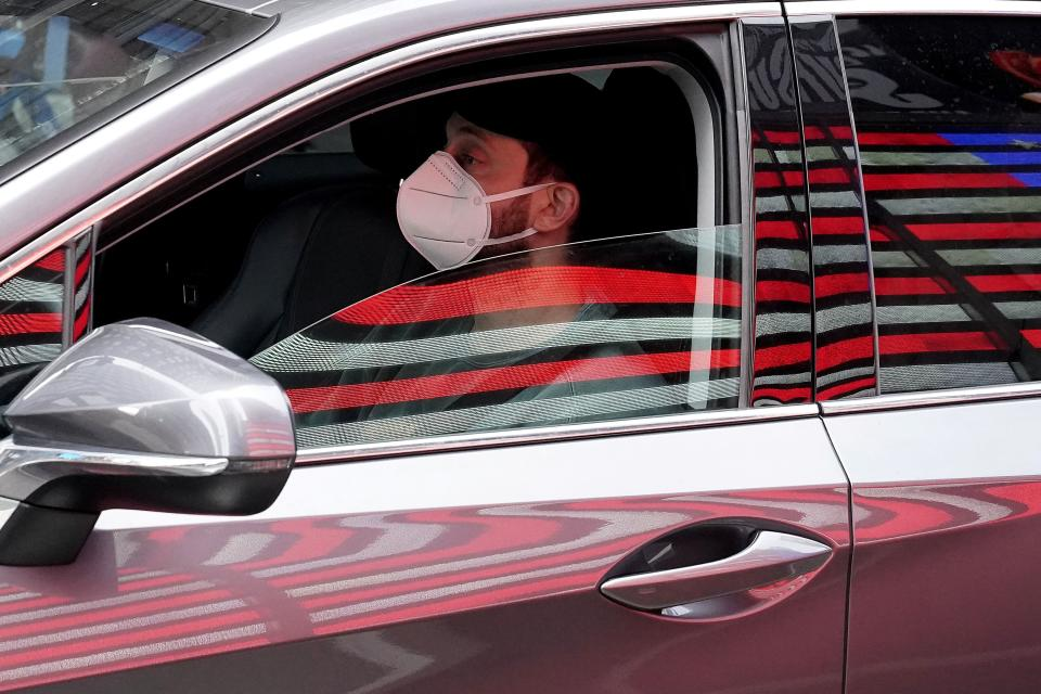 A man drives his car past a light flag while wearing a mask in Times Square during the coronavirus disease (COVID-19) pandemic in the Manhattan borough of New York City, New York, U.S., October 23, 2020. REUTERS/Carlo Allegri