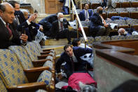 FILE - In this Jan. 6, 2021, file photo, people shelter in the House chamber as rioters try to break into the House Chamber at the U.S. Capitol in Washington. Months after Donald Trump's supporters besieged the Capitol, the ex-president and his supporters are revising their account of that day. (AP Photo/Andrew Harnik, File)