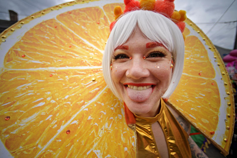 Reveler Anna Comarovschi is dressed as an orange slide as she marches in the St. Anne parade through the Marigny on Mardi Gras Day in New Orleans, Tuesday, Feb. 25, 2020.  (Max Becherer/The Advocate via AP)
