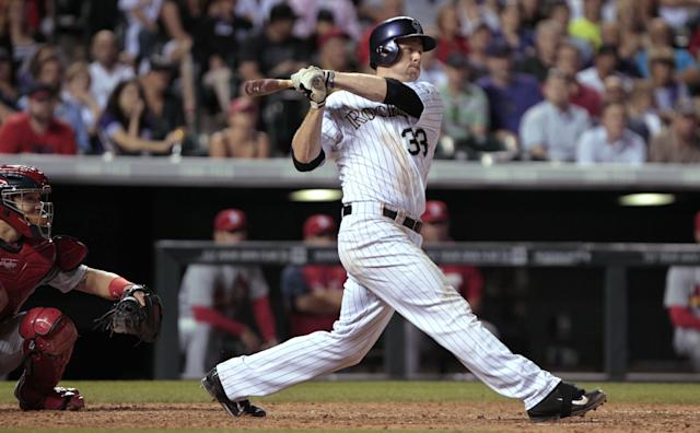Colorado Rockies' Justin Morneau follows through on a two-run single against the St. Louis Cardinals in the seventh inning of a baseball game in Denver on Tuesday, June 24, 2014. (AP Photo/Joe Mahoney)