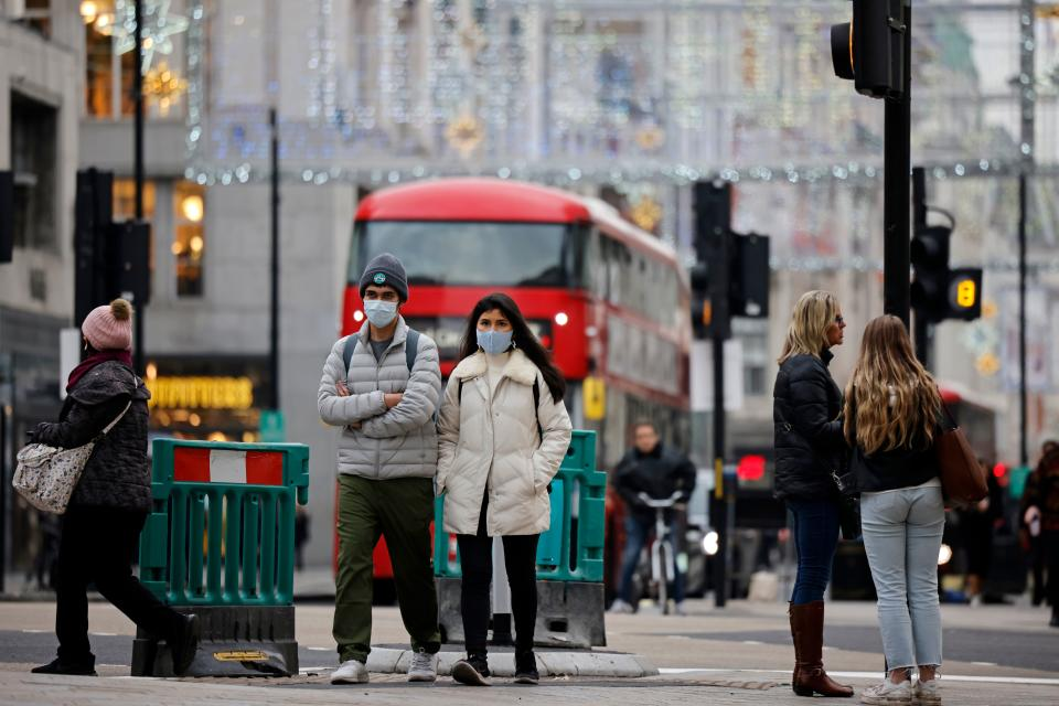 "Pedestrians wearing a protective face coverings to combat the spread of the coronavirus, walk down Oxford Street in central London on November 27, 2020, as life under a second lockdown continues in England. - England will return to a regional tiered system when the national stay-at-home order ends on December 2, and 23.3 million residents in the worst-hit areas are set to enter the ""very high"" alert level. (Photo by Tolga Akmen / AFP) (Photo by TOLGA AKMEN/AFP via Getty Images)"