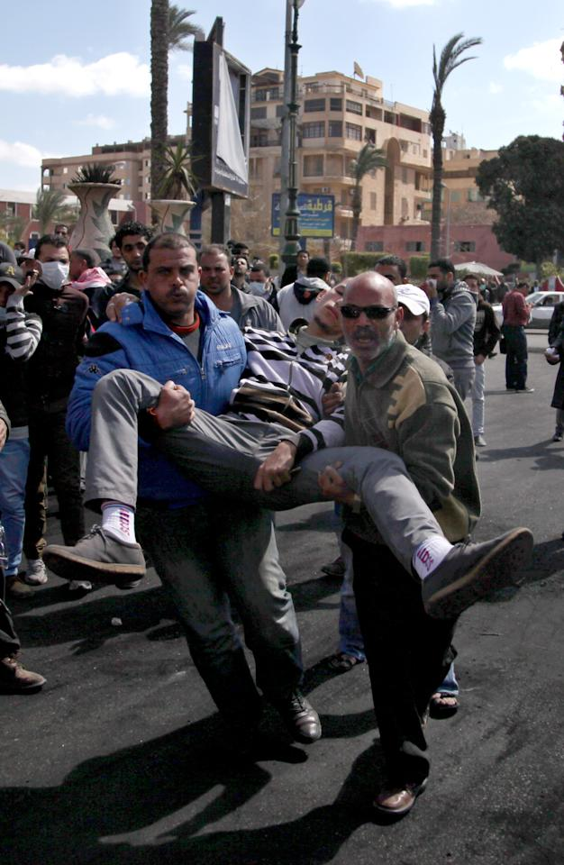 Egyptians evacuate a wounded man during clashes between protesters and riot police near the state security building in Port Said, Egypt, Wednesday, March 6, 2013. Clashes between protesters and police have broken out in this restive Egyptian port city despite efforts by the military to separate the two sides. (AP Photo/Khalil Hamra)