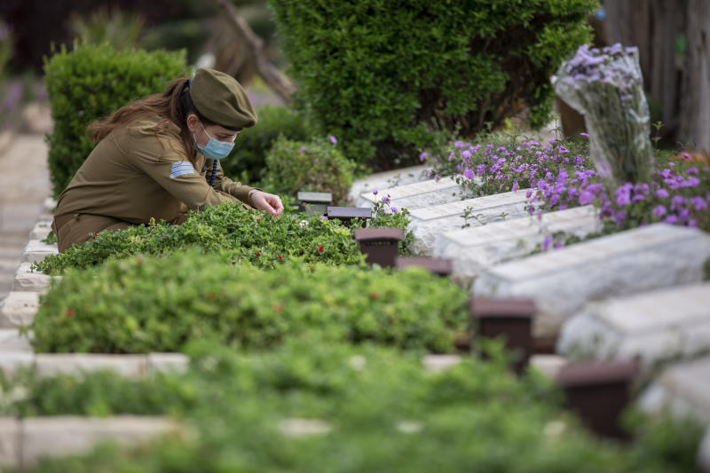 An Israeli soldier wearing a protective face mask amid concerns over the country's coronavirus outbreak, lights candles next to graves of fallen soldiers on the eve of memorial Day in Kiryat Shaul Military Cemetery in Tel Aviv, Israel, Monday, April 27, 2020. This year the government had banned public memorial services at military cemeteries as part of its measures to help stop the spread of the virus. Israel marks the annual Memorial Day in remembrance of soldiers who died in the nation's conflicts, beginning at dusk Monday until Tuesday evening. (AP Photo/Oded Balilty)