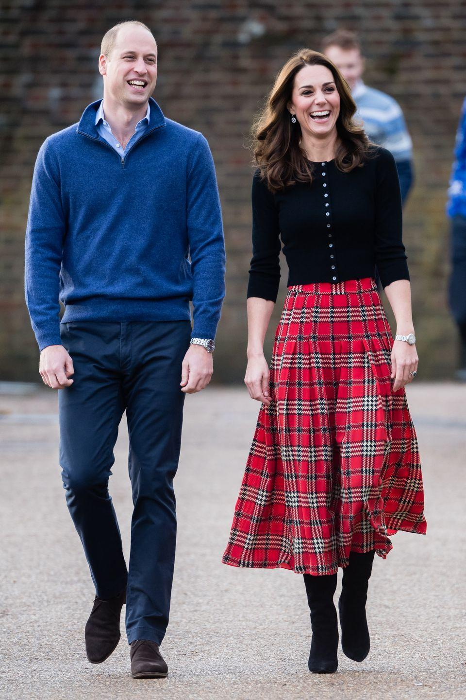 <p>Will and Kate are all smiles as they arrive at a Christmas party for military families in London. The Duchess looked festive in a plaid skirt by Emilia Wickstead with a black sweater by Brora.</p>