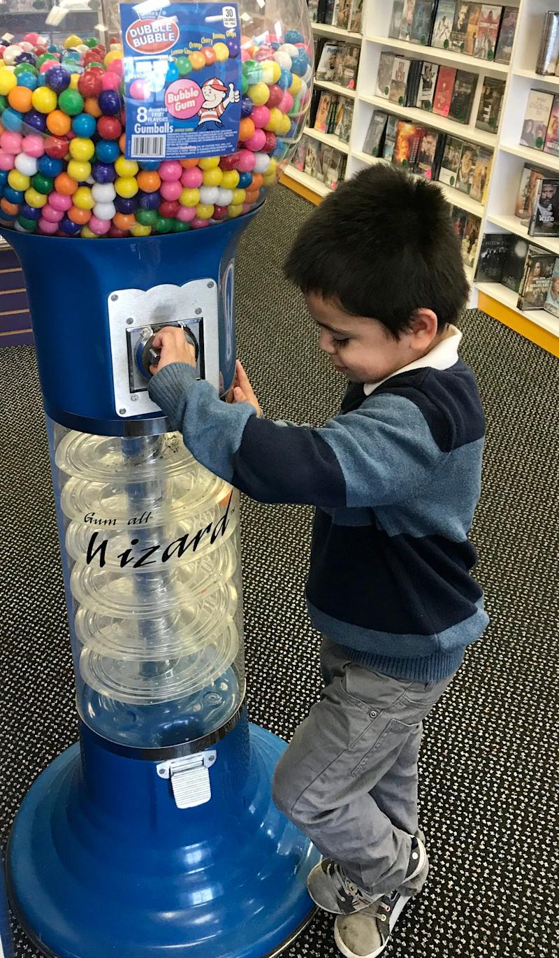 Juan Perez, 4, watches a giant gumball spiral through the Gumball Wizard.
