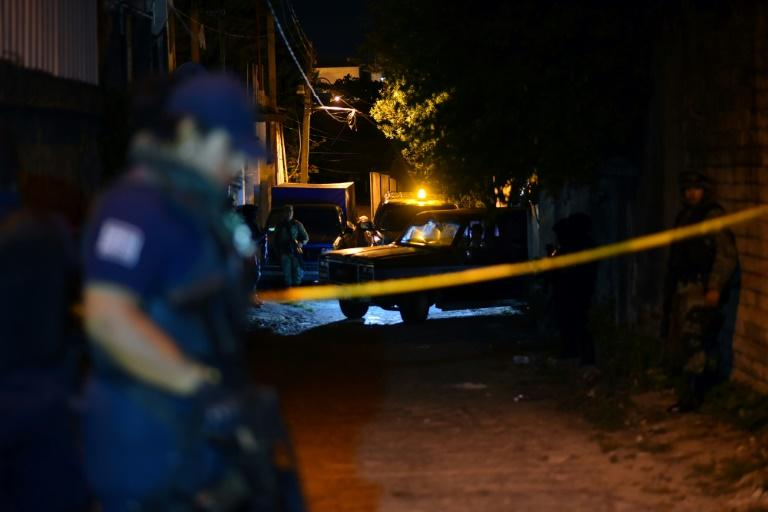 Police stand guard outside the setting of a party where 13 people were killed by unidentified gunmen