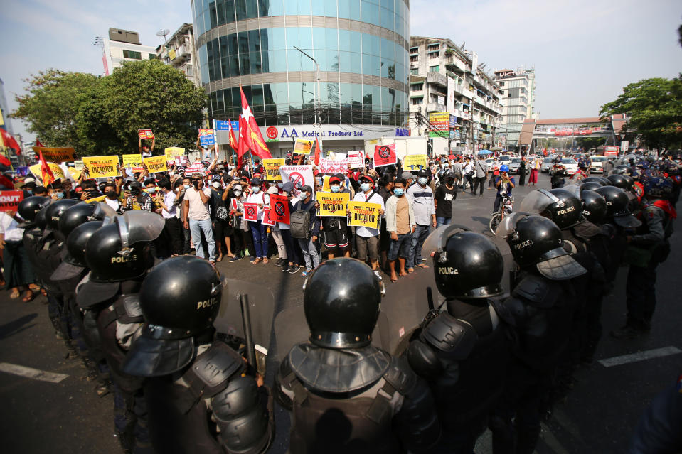 Anti-coup protesters face a row of riot police in Yangon, Myanmar Friday, Feb. 19, 2021. In the month since Feb. 1 coup, the mass protests occurring each day are a sharp reminder of the long and bloody struggle for democracy in a country where the military ruled directly for more than five decades. (AP Photo)
