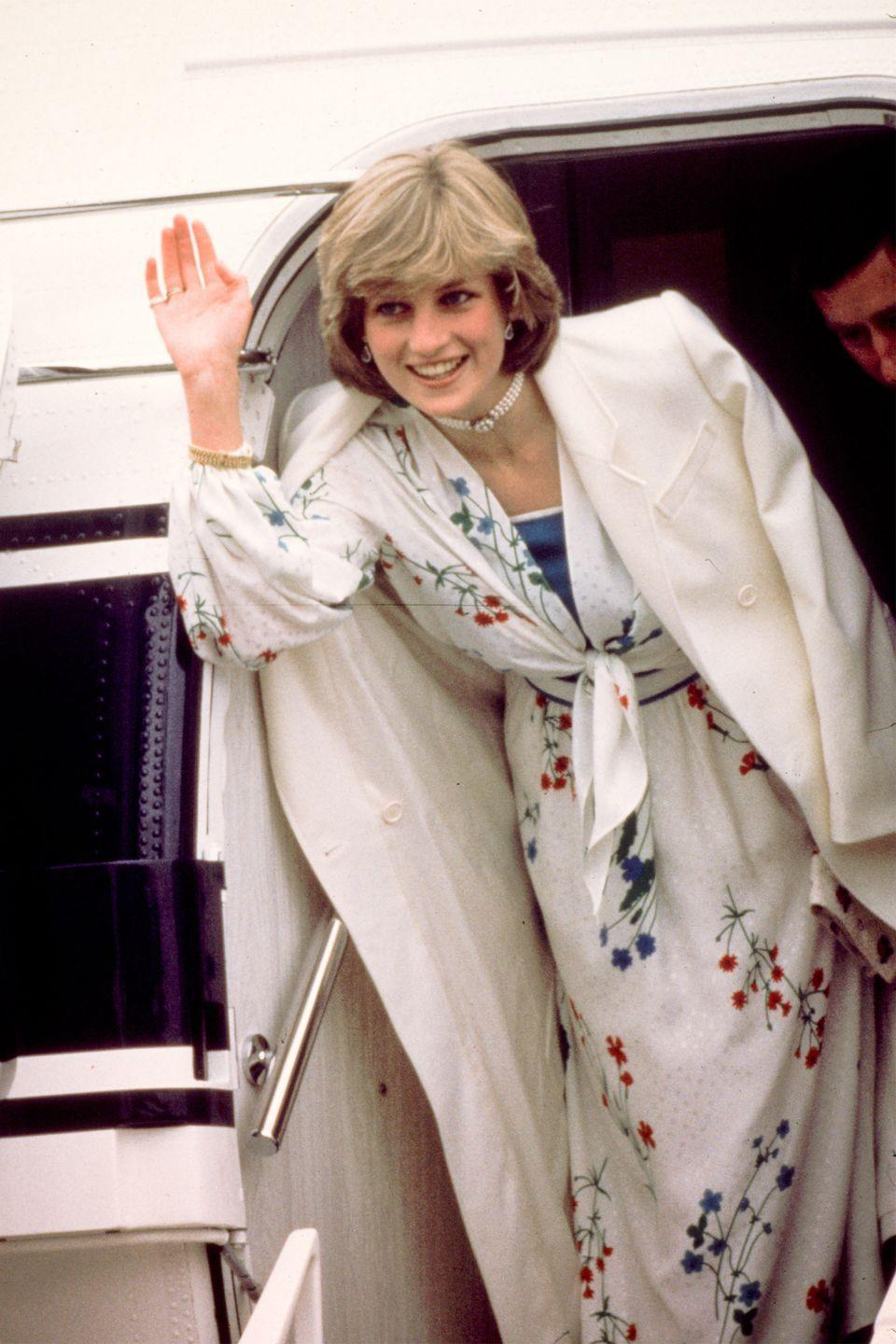 <p>In a floral wrap dress by Donald Campbell and white choker leaving Eastleigh airport in Hampshire to go on her honeymoon. </p>