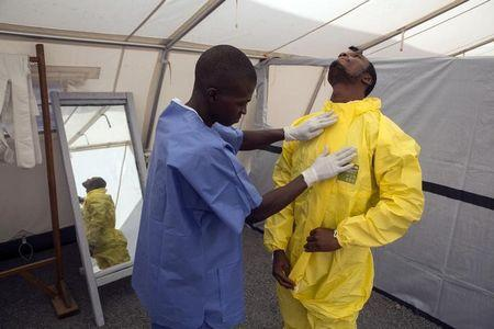 Health workers are pictured in protective gear before entering a quarantine zone at a Red Cross facility in the town of Koidu