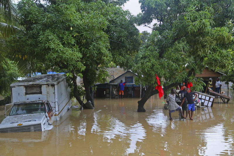 Residents of Leogane, Haiti find higher ground as the water level continues to rise Friday, Oct. 26, 2012. Residents of Leogane have had five consecutive days of rain in the aftermath of Hurricane Sandy, which caused serious flooding and claimed at least 26 lives in the impoverished country. (AP Photo/The Miami Herald, Carl Juste) MAGS OUT