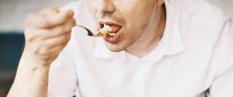 Unrecognizable man eating lunch. Front view. Horizontal.