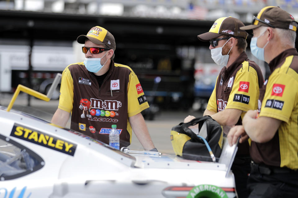 Crew members for driver Kyle Busch wait with his car before the start of the NASCAR Cup Series auto race Sunday, May 17, 2020, in Darlington, S.C. (AP Photo/Brynn Anderson)