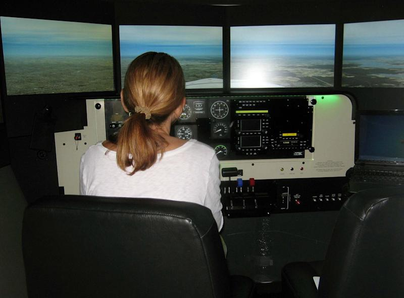 This 2012 photo supplied by the Menninger Clinic shows a woman using a flight simulator. The Menninger Clinic in Houston uses flight simulators in conjunction with cognitive behavioral therapy to help patients overcome fear of flying. (AP Photo/The Menninger Clinic, Douglas David Boyd)