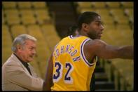Guard Earvin (Magic) Johnson of the Los Angeles Lakers looks on with Lakers owner Jerry Buss during a game.