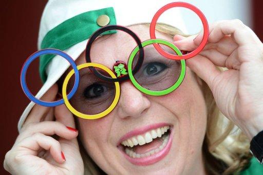 A spectator wearing glasses with Olympic rings arrives at the Olympic Park