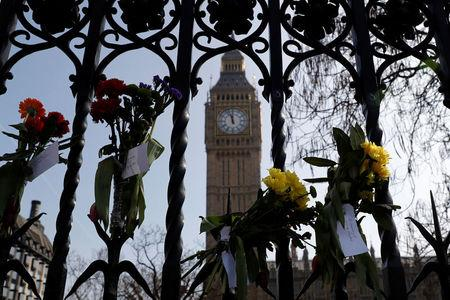 Floral tributes are attached to railings in Parliament Square following the attack in Westminster, central London