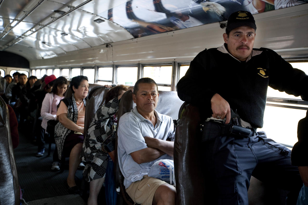 In this picture taken Friday Feb. 10, 2012, passengers ride on a public bus where a private guard stands guard in Guatemala City. President Otto Pérez Molina will meet on Monday with El Salvador's President Mauricio Funes to address issues related to regional security and how to coordinate their fight against organized crime. Perez has blamed the drug cartels for the high levels of violence in his country of 13 million overrun by gangs and the Mexican cartels, with a rate of 41 homicides per 100,000 inhabitants, nearly three times that of neighboring Mexico. (AP Photo/Rodrigo Abd)