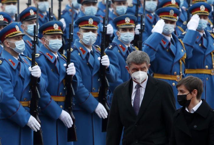 Czech Prime Minister Andrej Babis, centre, reviews the honor guard during a welcome ceremony with his Serbian counterpart Ana Brnabic, right, before their official talks at the Serbia Palace in Belgrade, Serbia, Wednesday, Feb. 10, 2021. Babis is on a one-day official visit to Serbia. (AP Photo/Darko Vojinovic)