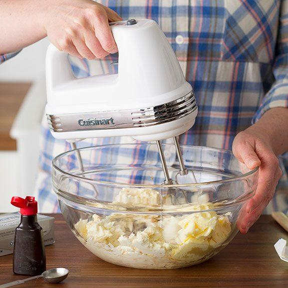 Person just beating the ingredients in a glass bowl with a hand mixer with a small container of vanilla extract nearby