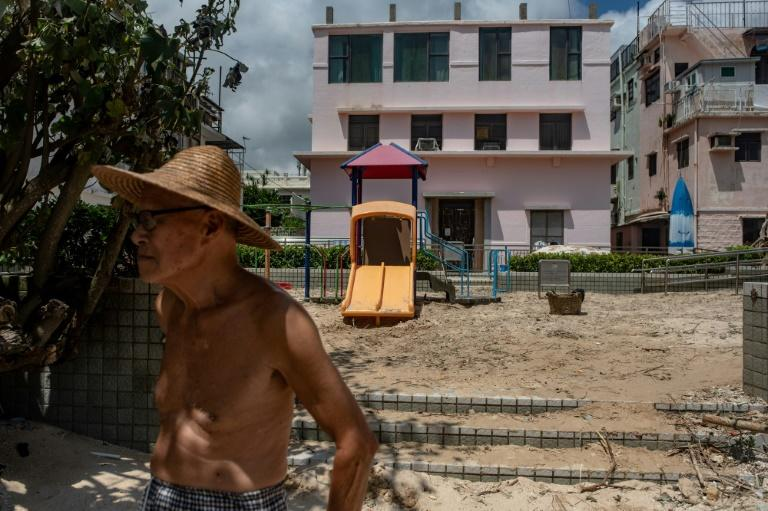 A man stands in front of a playground filled with sand in Shek O