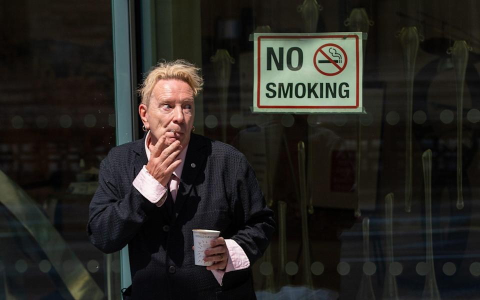 John Lydon, aka Johnny Rotten, smokes outside the Rolls Building at the High Court, London - PA