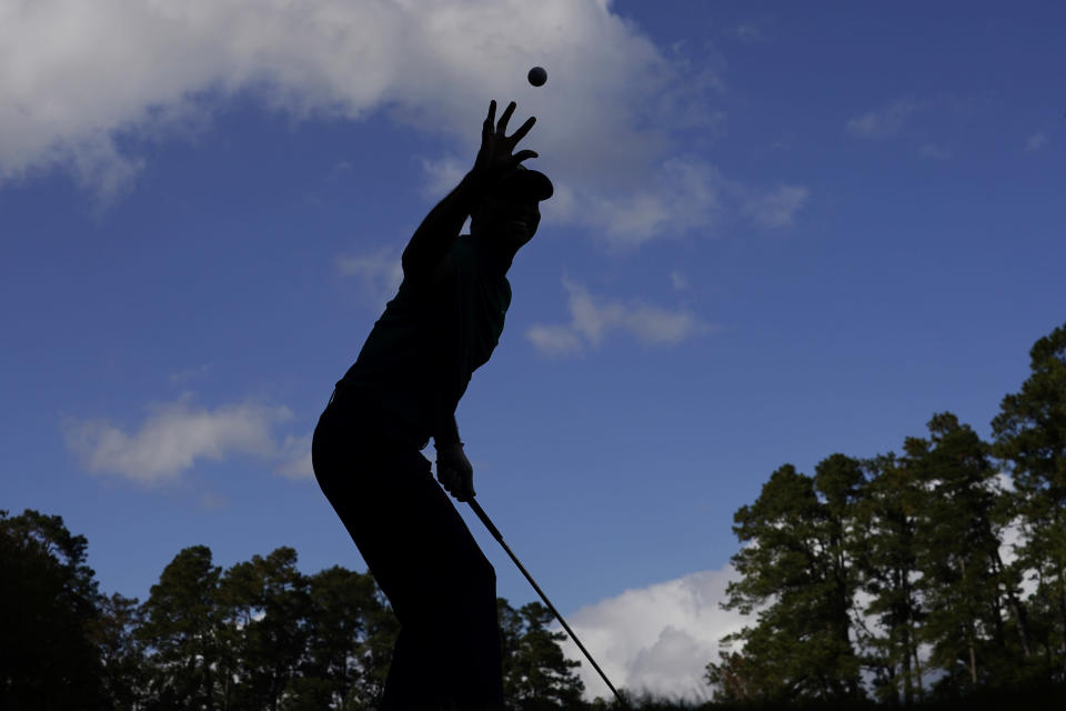 Tiger Woods catches a ball from his caddie before teeing off on the 16th hole during a practice round for the Masters golf tournament Monday, Nov. 9, 2020, in Augusta, Ga. (AP Photo/Charlie Riedel)
