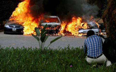 <span>Cars are seen on fire at the scene of explosions and gunshots in Nairobi</span> <span>Credit: REUTERS/Thomas Mukoya </span>