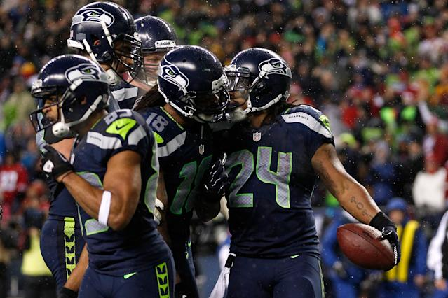 SEATTLE, WA - DECEMBER 23: Marshawn Lynch #24 of the Seattle Seahawks celebrates with teammates including Sidney Rice #18 after Lynch scored a 9-yard touchdown catch in the first quarter against the San Francisco 49ers at Qwest Field on December 23, 2012 in Seattle, Washington. (Photo by Otto Greule Jr/Getty Images)