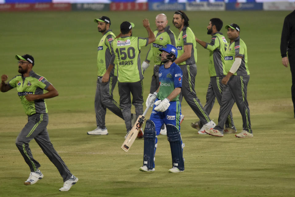Multan Sultans batsman Adam Lyth, in blue, walks back while Lahore Qalandars pacer David Wiese, third right back, celebrate with teammates after the Lyth's dismissal during the second eliminator cricket match of Pakistan Super League T20 cup at National Stadium in Karachi, Pakistan, Sunday, Nov. 15, 2020. (AP Photo/Fareed Khan)