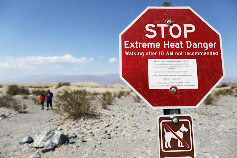 DEATH VALLEY NATIONAL PARK, CALIFORNIA - AUGUST 17: Visitors walk near a sign warning of extreme heat danger on August 17, 2020 in Death Valley National Park, California. The temperature reached 130 degrees at Death Valley National Park on August 16, hitting what may be the hottest temperature recorded on Earth since at least 1913, according to the National Weather Service. Park visitors have been warned, 'Travel prepared to survive.' (Photo by Mario Tama/Getty Images)