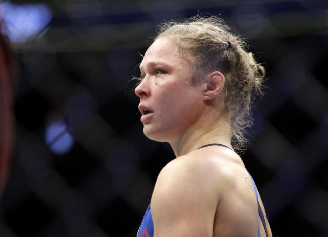 FILE - In this Dec. 30, 2016, file photo, Ronda Rousey stands in the cage after Amanda Nunes forced a stoppage in the first round of their women's bantamweight championship mixed martial arts bout at UFC 207 in Las Vegas. The former UFC champion Rousey could soon make the move to WWE. Shes met with WWE executives and has seemed excited about the possibility of becoming a wrestler. Rousey may not debut at one of WWEs signature events this weekend in Philadelphia because shes filming a movie in Colombia. (AP Photo/John Locher, File)