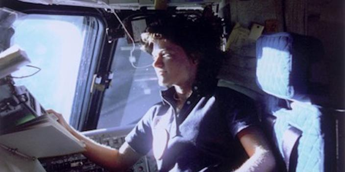 Sally Ride looking looks out of the space shuttle window on her first trip to space in 1983.