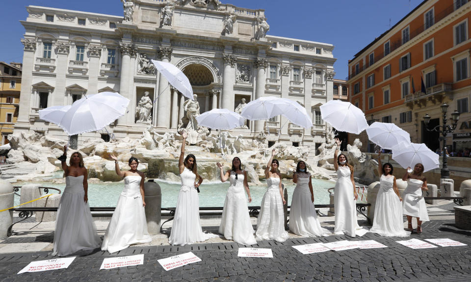 Women whose wedding ceremony was delayed or canceled due to restrictions caused by COVID-19 pandemic stage a protest at the Trevi Fountain in Rome, Tuesday, July 7, 2020. (AP Photo/Riccardo De Luca)
