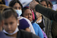 Migrant women are asked to line up for a free meal at a makeshift camp at the border port of entry leading to the United States, Friday, March 12, 2021, in Tijuana, Mexico. The migrant camp shows how confusion has undercut the message from U.S. President Joe Biden that it's not the time to come to the United States. Badly misinformed, some 1,500 migrants who set up tents across the border from San Diego harbor false hope that Biden will open entry briefly and without notice. (AP Photo/Gregory Bull)