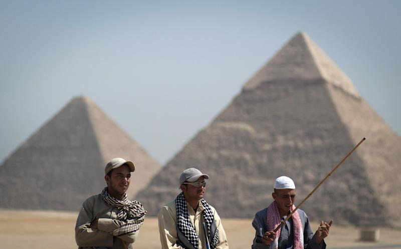 In this Thursday, Sept. 27, 2012 photo, tour guides wait for clients next to the Giza pyramids, near Cairo, Egypt. The Egyptian demonstrations against an online film that was produced by a U.S. citizen originally from Egypt and denigrates the Prophet Muhammad were part of a wider explosion of anger in Muslim countries. They happened near the U.S. Embassy, far from the pyramids of Giza on Cairo's outskirts, and a lot further from gated Red Sea resorts, cocoons for the beach-bound vacationer. Yet the online or TV images _ flames, barricades, whooping demonstrators _ are a killjoy for anyone planning a getaway, even though the protests have largely subsided. Tour guides in Egypt say tourist bookings are mostly holding, but they worry about a dropoff early next year, since people tend to plan several months ahead.(AP Photo/Khalil Hamra)