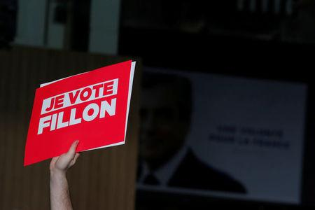 A supporter of the French centre-right presidential candidate Francois Fillon holds a placard reading 'I vote for Fillon', at a political rally in Paris, France, April 9, 2017. REUTERS/Benoit Tessier A suppo