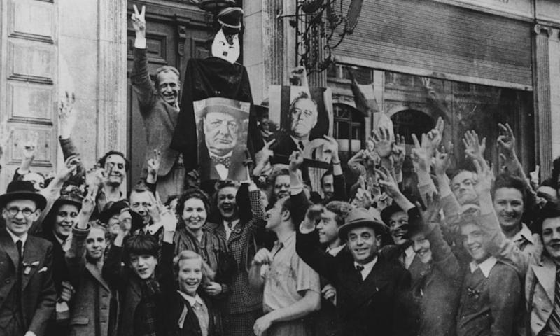 A jubilant crowd bearing images of Churchill and Roosevelt gathers outside the home of a Nazi collaborator in Brussels to celebrate the liberation of Belgium by Allied forces