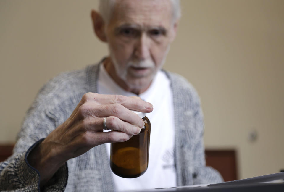In this May 3, 2019, photo, Robert Fuller looks at the vial containing the drugs that will end his life a week later as he is counseled about it at a compounding pharmacy in Seattle. The day he picked to die, Fuller had the party of a lifetime. Then later that afternoon, he plunged two syringes filled with a fatal drug cocktail into a feeding tube in his abdomen. He's one of about 1,200 people who have used Washington's Death with Dignity Act to end their lives in the decade since it became law. (AP Photo/Elaine Thompson)