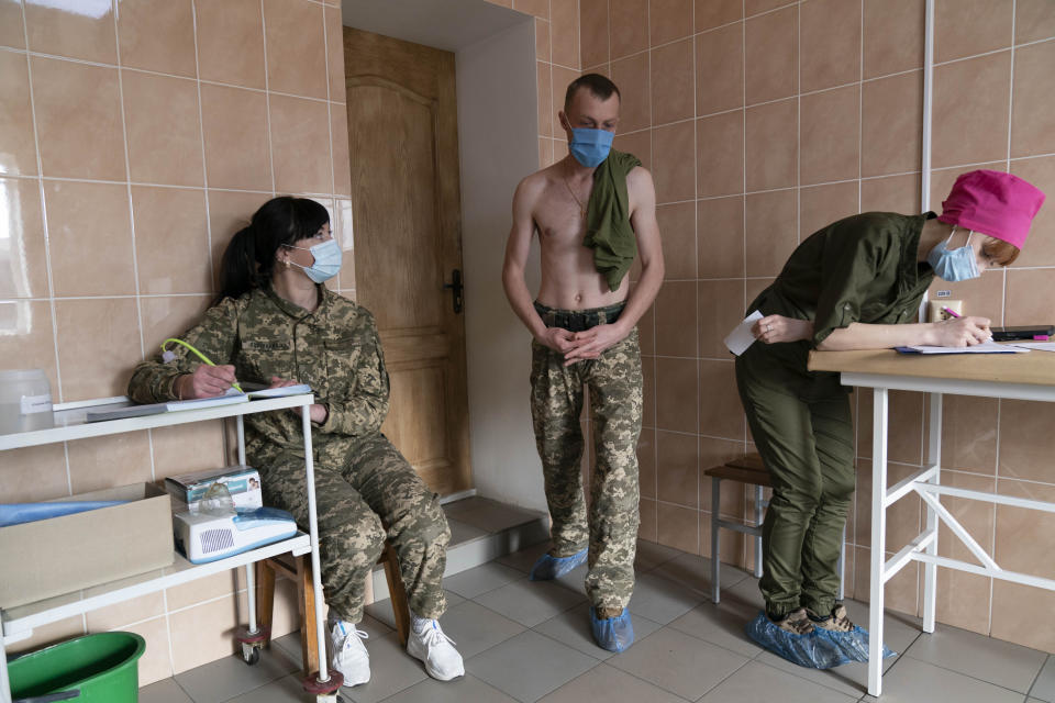 A Ukrainian serviceman waits to receive a dose of the AstraZeneca COVID-19 vaccine marketed under the name CoviShield at a military base in Kramatorsk, Ukraine, Tuesday, March 2, 2021. Ukraine plans to vaccinate 14.4 million people this year, or about 35% of its 41 million people. (AP Photo/Evgeniy Maloletka)