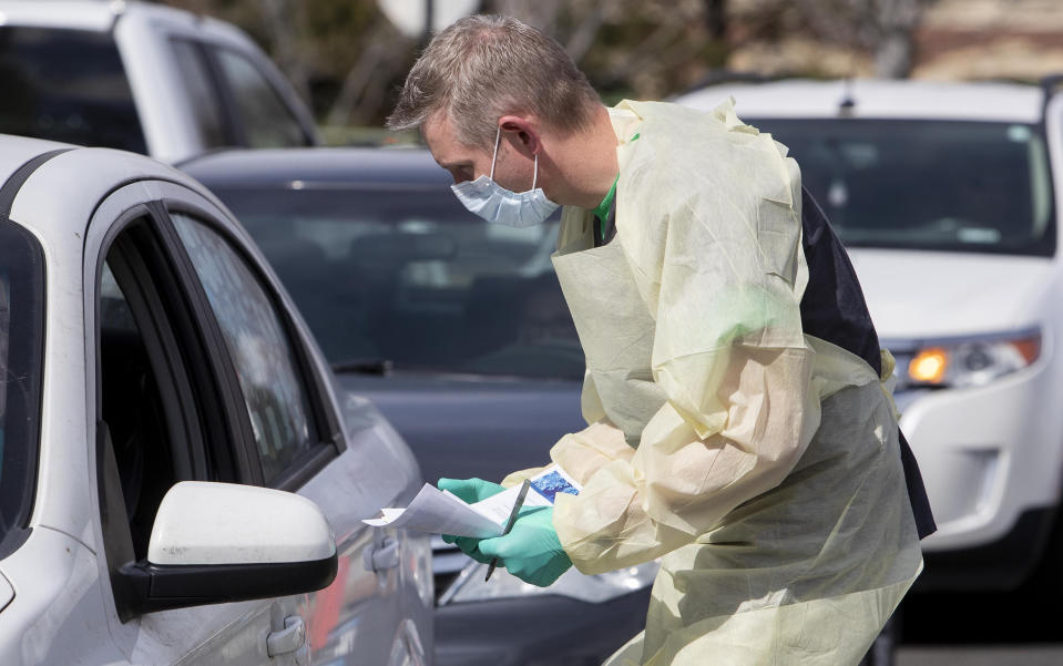 Nurse Manager Cullen Anderson, RN, checks people in a line of cars waiting to be tested for the COVID-19 coronavirus at a drive-thru testing station at St. Luke's Meridian Medical Center on Tuesday, March 17, 2020. (Darin Oswald / Idaho Statesman / Tribune News Service via Getty Images)