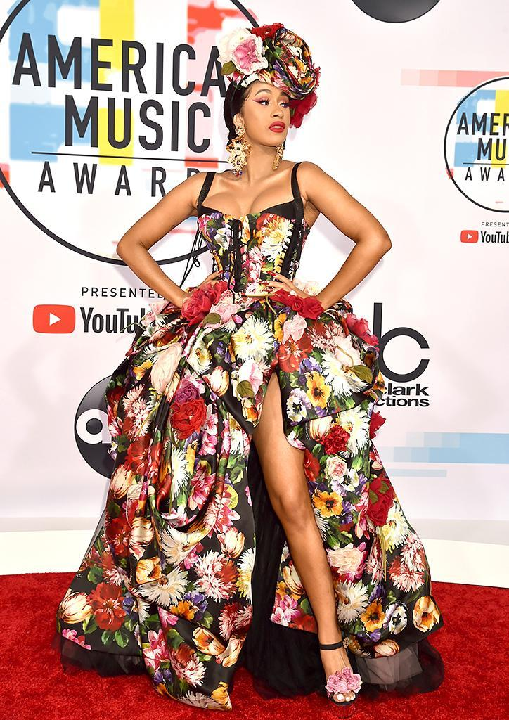 <p>Cardi B has arrived. The rapper, who snagged the first award of the night, pulled out all the stops with a floral number and matching headpiece and sandals. (Photo: Jeff Kravitz/FilmMagic) </p>
