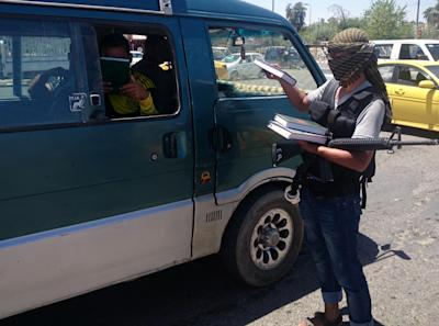A fighter with the al-Qaida-inspired Islamic State of Iraq and the Levant (ISIL) distributes a copy of the Quran, Islam's holy book, to a driver in central northern city of Mosul, 225 miles (360 kilometers) northwest of Baghdad, Iraq, Sunday, June 22, 2014. Sunni militants on Sunday captured two border crossings, one along the frontier with Jordan and the other with Syria, security and military officials said, as they pressed on with their offensive in one of Iraq's most restive regions. (AP Photo)