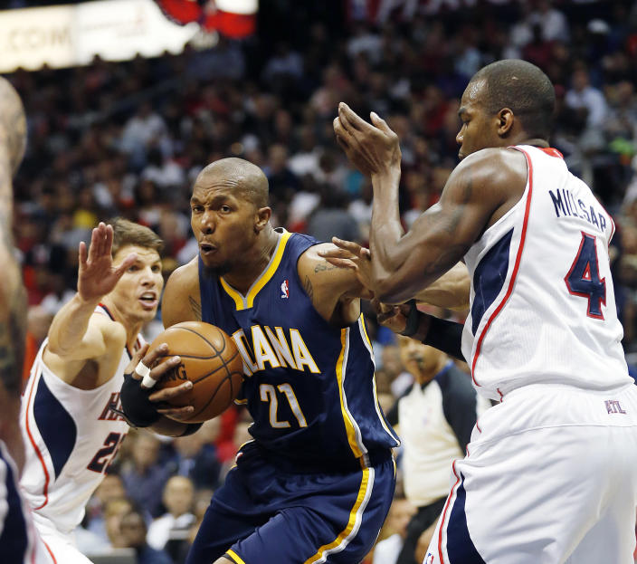 Indiana Pacers forward David West (21) drives between Atlanta Hawks guard Kyle Korver, left, and forward Paul Millsap (4) in the first half of Game 3 of an NBA basketball first-round playoff series on Thursday, April 24, 2014, in Atlanta. (AP Photo/John Bazemore)