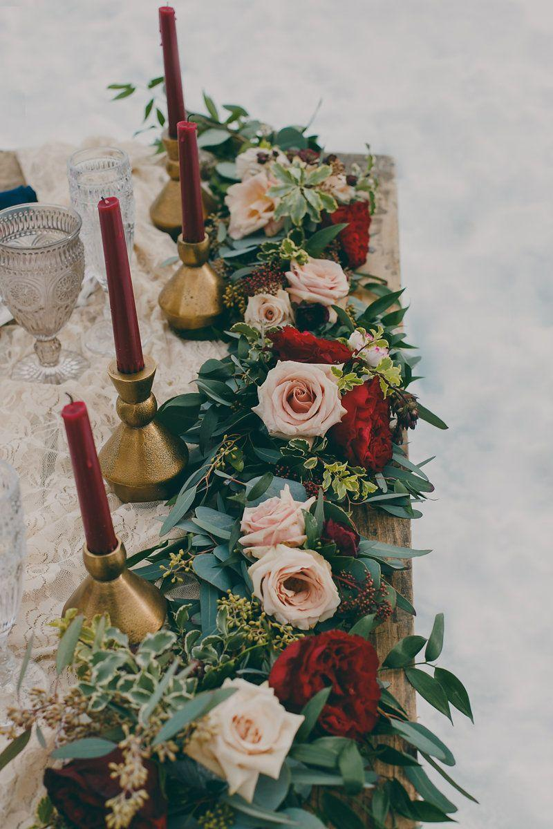 "<p>A garland centerpiece adds a wisp of whimsy and romance to practically any table. This garland incorporates pastel pink roses and deep red flowers—which echo the jewel tone of the candles—for a holiday centerpiece that is equal parts traditional and contemporary. </p><p><em>Via <a href=""http://junebugweddings.com/wedding-blog/passionate-winter-elopement-inspiration-emerald-lake/"" rel=""nofollow noopener"" target=""_blank"" data-ylk=""slk:Junebug Weddings"" class=""link rapid-noclick-resp"">Junebug Weddings</a></em></p>"