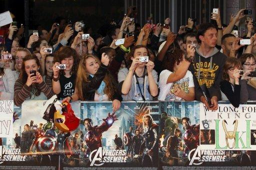 Film fans take photographs during the Marvel Avengers Assemble European Premiere