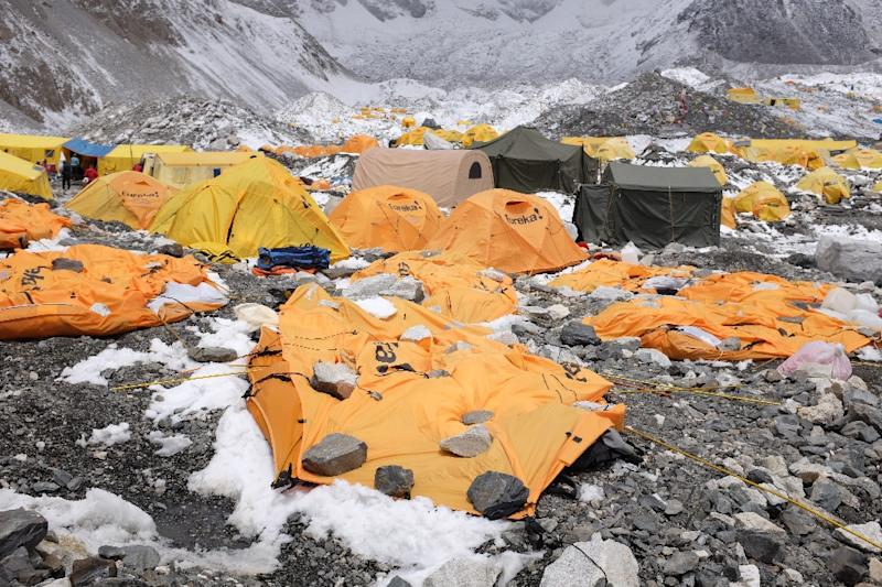 Rocks are kept over flattened tents at Everest Base Camp to cover the bodies of some of the people that died in the earthquake-triggered avalanche, April 26, 2015 (AFP Photo/Roberto Schmidt)